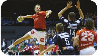 Foto de um jogador se preparando para arremessar a bola que segura com uma das mãos.