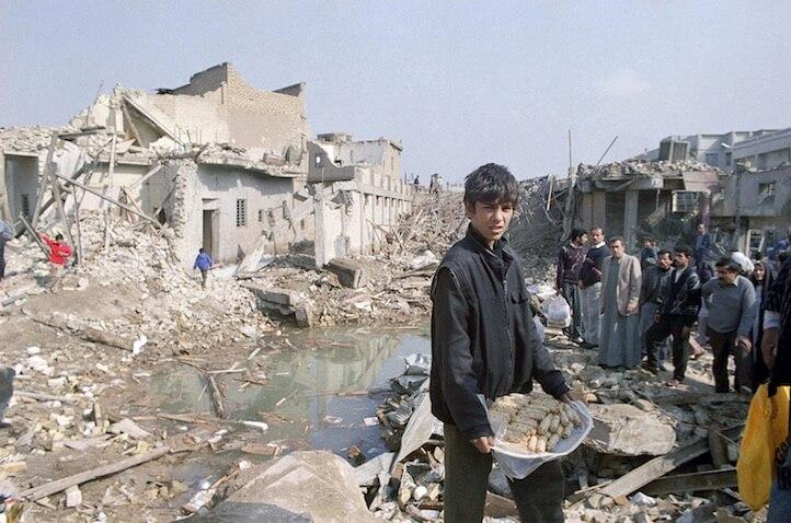 Um jovem iraquiano carregava um prato de salsicha nas ruínas das casas em uma área a oeste da ponte Al-Ahrar.
