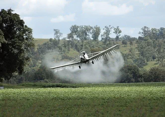 Avião jogando agrotóxico em uma plantação.