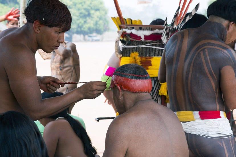 Índios pintando o corpo.