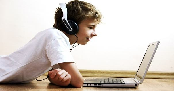 Menino ouvindo com fones de ouvido em inglês