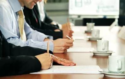 Pessoas escrevendo atas em uma reunião