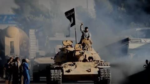 Combatente do Estado Islâmico em um tanque de guerra.
