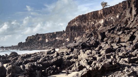 Foto das falésias com grandes paredões de pedra rentes ao mar.