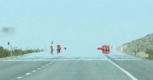 Miragem inferior que ocorre no asfalto em dias quentes.