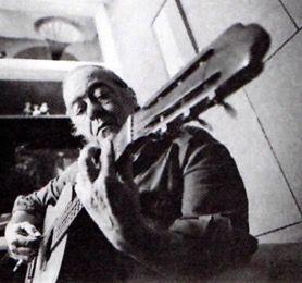 Retrato de Vinicius de Moraes tocando um violão.