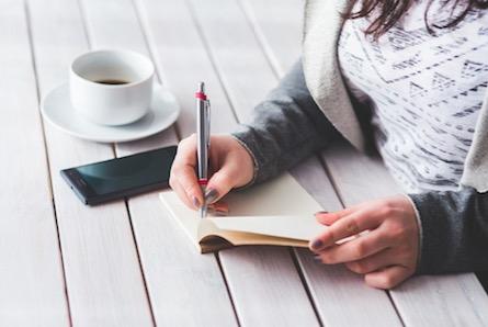 Mulher fazendo anotações em um caderno.