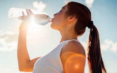 Mulher bebendo água de uma garrafa.