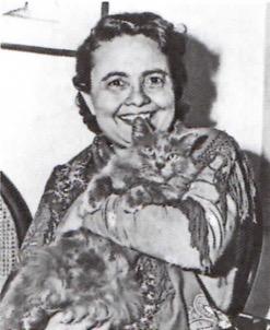 Fotografia em preto e branco de Raquel de Queiroz segurando seu gato de estimação.