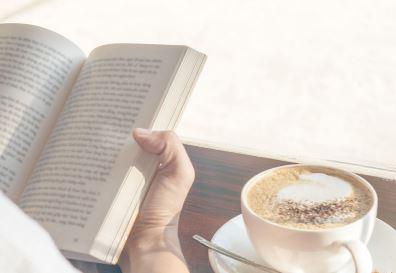 Uma pessoa lendo um livro com uma xícara de café ao lado.