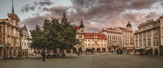 Fotografia de uma praça central de praga e seus prédios históricos ao redor.
