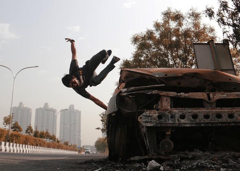 Homem praticando parkour em um carro abandonado.