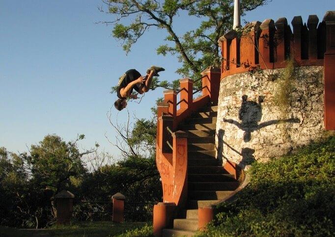 Homem praticando parkour em uma escada.