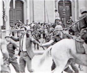 Foto do protesto onde um policial agride um manifestante.