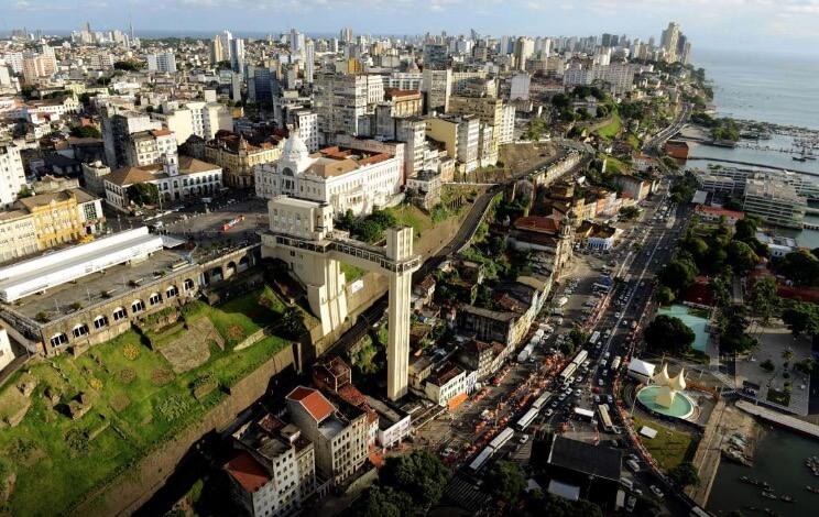 Foto da cidade alta e baixa de Salvador, com o elevador Lacerda ao fundo.