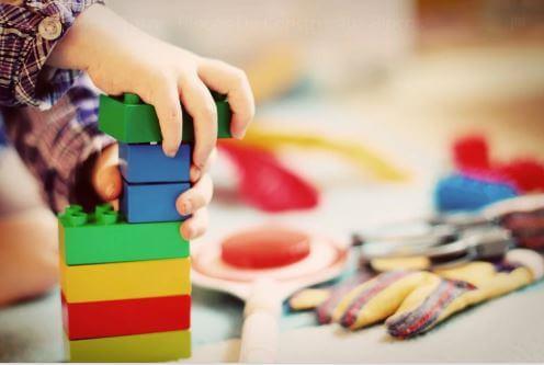 Criança empilhando um brinquedo.