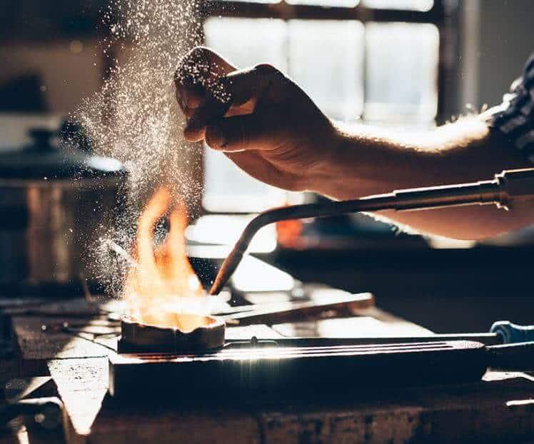 Um ourives fabricando uma joia.