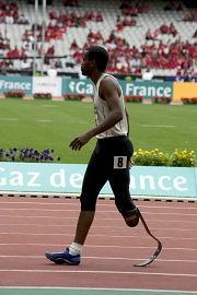 Atleta paraolímpico de atletismo usando uma prótese de corrida.