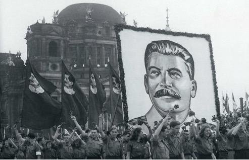 Retrato de Stalin sendo erguido na multidão na URSS